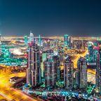 Die beleuchteten Wolkenkratzer lassen Dubais Skyline bei Nacht erstrahlen.