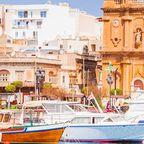 Valletta mit Booten im Vordergrund und Kirchenreflektion im Wasser