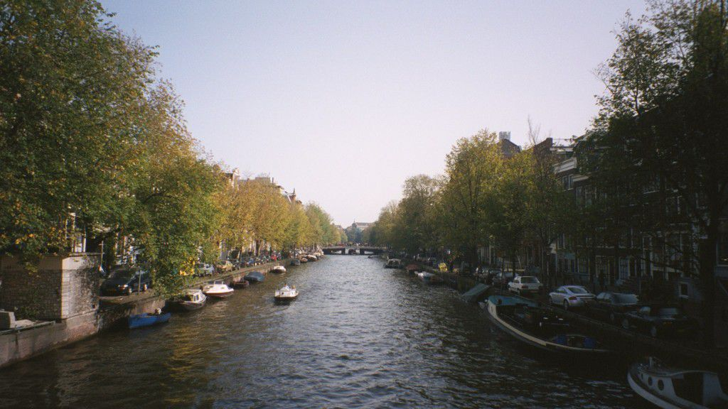 Amsterdam-canal-trees-autumn-colours-many-small-boats-moored-bridge-1-MY.jpg