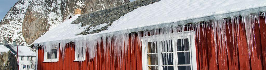 Eiszapfen auf dem Dach eines roten Hauses in Norwegen