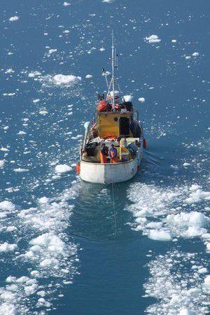Fischerboot bahnt sich seinen Weg durchs Eis